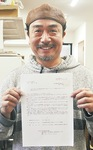 受賞の知らせを手に喜ぶ石川さん