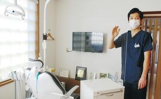 診療室に設置したアクリル板を紹介する佐藤院長