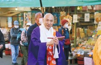 お練りの際、観光客らに挨拶する佐藤新貫首