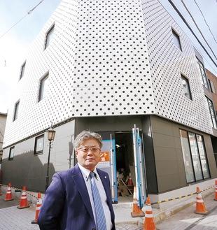 完成間近のビルの前に立つ谷口社長