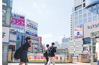 八王子駅前の温度計が気温34度を示している=19日撮影