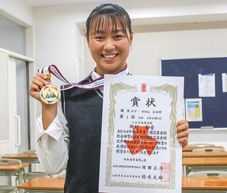 メダルと賞状を掲げる岡村さん