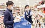 福島店長(右)の指示の下、商品を陳列する上田選手