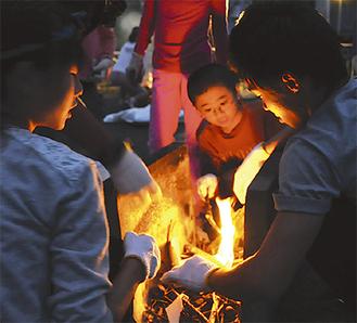 学生の指導のもと校庭で火おこしを体験(写真は瓜生小学校)