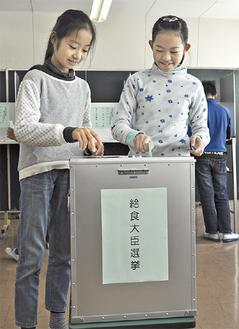 本物の投票箱を使って投票を行う児童たち