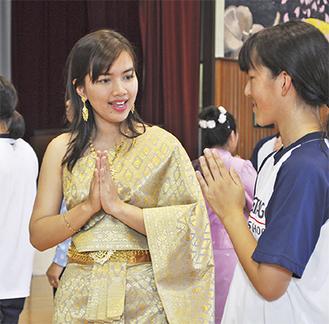 生徒に挨拶の仕方を教えるタイの教員(左)