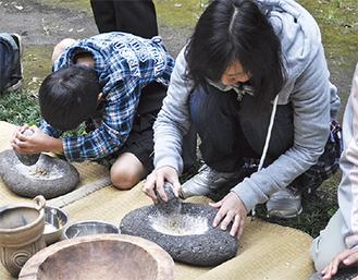 石を使って木の実をすりつぶす参加者