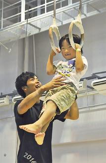 体操のつり輪を体験する男の子