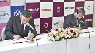 確認書にサインをする阿部市長(左)と桜美林学園の佐藤理事長