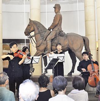 明治天皇騎馬像の前で演奏する谷本氏(左)