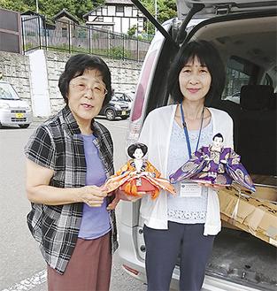 浪江町教育委員会の職員に手渡す長谷さん(左)