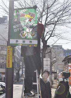 街路灯にフラッグを取り付けるサポーター