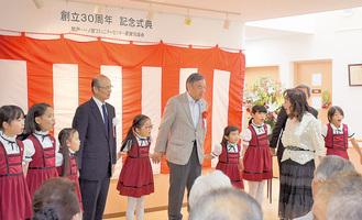 多摩ファミリーシンガーズの子どもたちと一緒に歌う片倉会長(左から4人目)と阿部市長(同6人目)