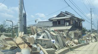 洪水被害を受けた真備町。家の窓がなく道端に家具の残骸が積み上げられている=松浦さん撮影