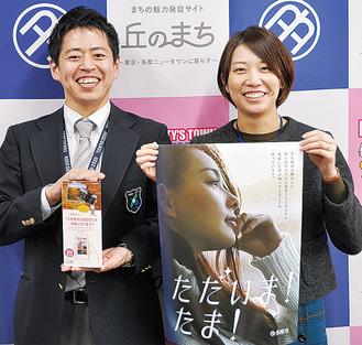 ポスターとPOPをもつ広報課の齋郷さん(左)と堀川さん