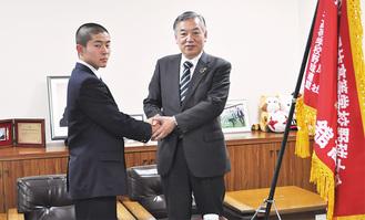 選抜旗の横で市長と握手をする松室主将