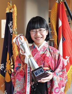 2本の優勝旗とトロフィーを手に笑顔を見せる矢島さん