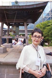 ニューヨークの国連本部中庭にある「平和の鐘」と高瀨さん=週刊NY生活提供