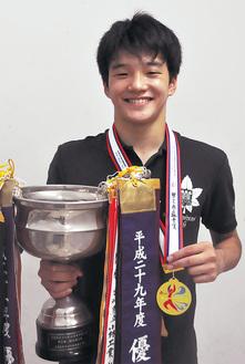メダルとトロフィーを手に笑顔を見せる森谷さん