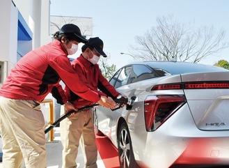 開所式で燃料電池自動車(FCV)へ充填するステーションスタッフ