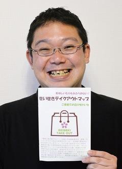 制作した小冊子を手にする塩田さん