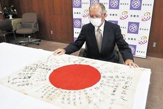 返還された出征旗を見つめる田中政幸さん
