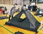体育館でテントを張る児童たち