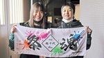 自分たちでデザインしたタオルを手にする実行委員長の横山さん(左)と副実行委員長の大迫さん