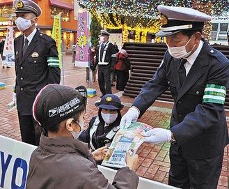 反射材と啓発チラシを配布する千田拓雄交通安全協会会長