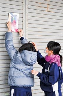 シャッターにポスターを貼る生徒たち
