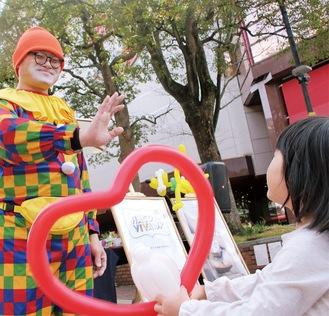 ハート型のバルーンを子どもに手渡すピエロ