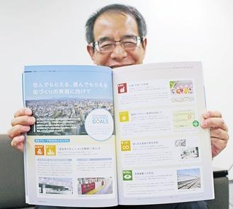 取組みをまとめた冊子を見せる京王電鉄の吉田さん