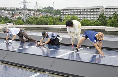 屋上で太陽光パネル清掃