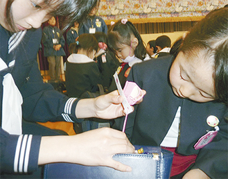 バッグにミニランドセルを付ける中学生。右は幼稚園児