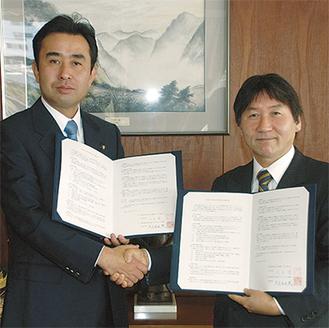 協定書を交わし握手する大木市長(右)と大豆生田足利市長(左)