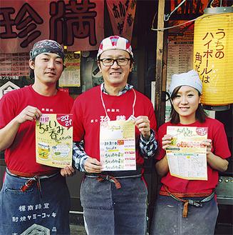 運営本部でもある珍満の前でスタッフと共にイベントをPRする菊地努委員長(中央)