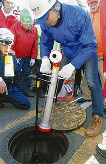 訓練で消火栓への接続を体験する参加者 =20日・南林間中央公園