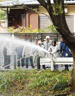 引地川に向かって放水する参加者