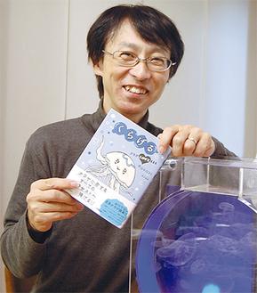 特注のくらげ専用水槽の前で著書を紹介する平山さん