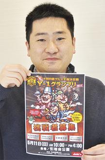 ポスターを手にする石田健実行委員長