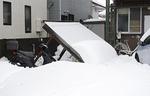 雪の重みで倒れる屋根=15日午後1時頃 南林間