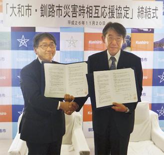 締結式で握手を交わす大木市長(左)と蛯名大也・釧路市長