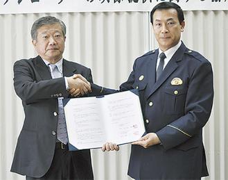 締結式で調印し、握手をする松川敬署長(右)と入江公敏代表者(左)