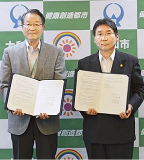 協定書を手にする佐瀬理事長(左)と大木市長