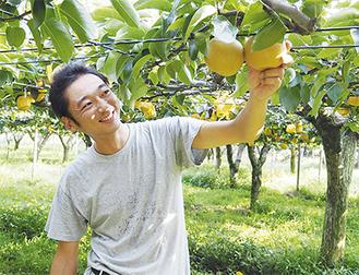 自慢の梨を片手に微笑む神谷さん