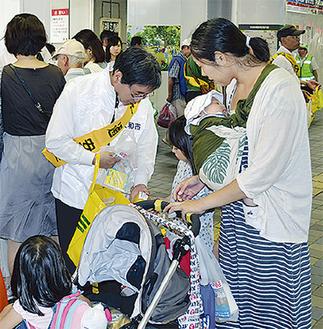 駅を通行する親子に梨を配る大木市長