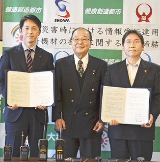 協定書を手に撮影に応じる(左から)武田社長、武田会長、大木市長