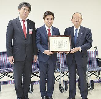 車いすを背に、感謝状を手にする(左から)岡田理事長と林委員長、高橋会長
