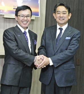 握手する冨安社長(左)と角野代表取締役(右)