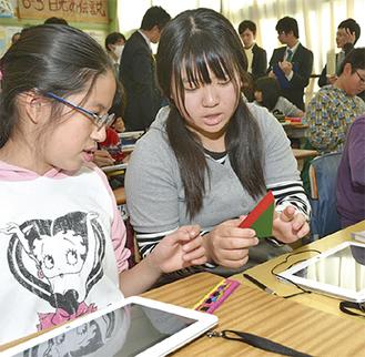 タブレットを使い、三角柱の体積について考える児童たち